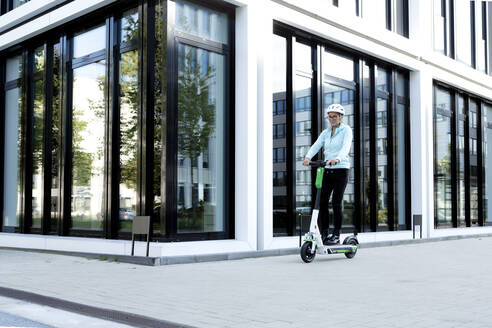 Mature woman riding electric scooter in the city - FLLF00297