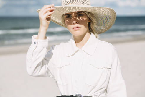 Portrait of blond young woman wearing white shirt and summer hat on the beach - JESF00332