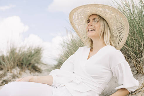 Portrait of blond young woman lying in beach dunes wearing white wrap blouse and summer hat - JESF00338