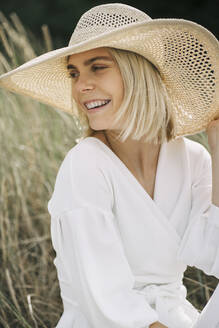 Portrait of blond young woman in dunes wearing white wrap blouse and summer hat - JESF00344