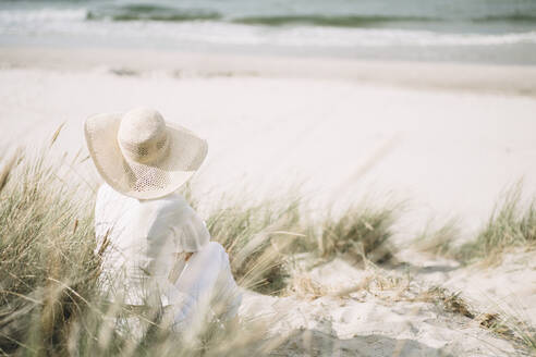 Back view of woman wearing summer hat sitting on the beach looking at the sea, Ruegen, Germany - JESF00347