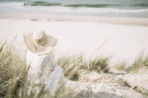 Rückenansicht: Junge Frau mit Sonnenhut am Strand, Rügen, Deutschland - JESF00347