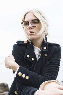 Portrait of blond young woman wearing glasses and coat - JESF00353