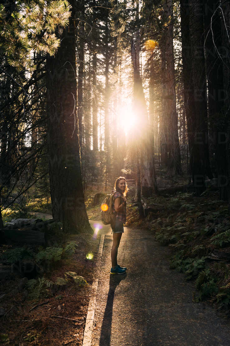 Woman with backpack hiking in the forest at sunset in Sequoia National Park, California, USA - GEMF03171 - Gemma Ferrando/Westend61