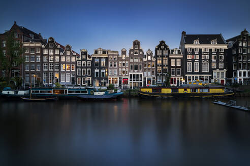 Netherlands, Amsterdam, Various boats moored along city canal with row of houses in background - XCF00232