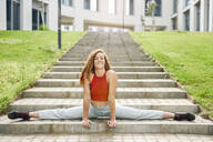 Young woman doing the splits on outdoor stairs - JSMF01271