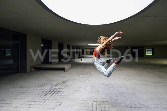 Sporty young woman jumping in courtyard - JSM01274 - Javier Sánchez Mingorance/Westend61