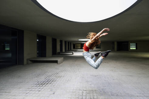 Spain, Andalusia, Granada. Acrobatic redheaded woman, doing outdoor acrobatics near modern buildings. Fitness concept. - JSM01274