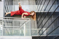 Sporty young woman doing acrobatics on a railing - JSMF01280