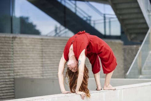 Sporty young woman doing acrobatics on a concrete wall - JSMF01283