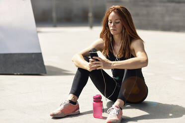 Sporty young woman with earphones having a break using smartphone outdoors - JSMF01292
