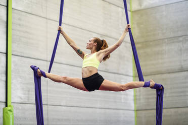 Young woman doing aerial silk in an exercise room - JSMF01301