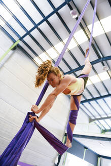 Young woman doing aerial silk in an exercise room - JSMF01304
