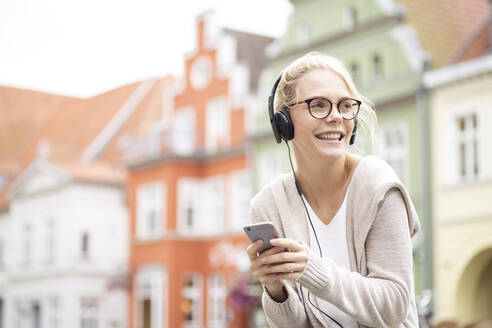 Portrait of blond woman using smartphone and headphones - JESF00363