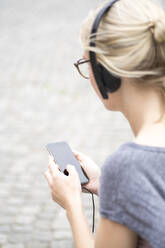 Portrait of blond woman using smartphone and headphones - JESF00366