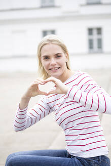 Portrait of young blond woman making heart shape with hands and fingers - JESF00378