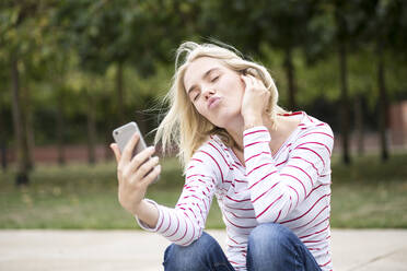 Portrait of blond woman using smartphone and taking a selfie - JESF00381