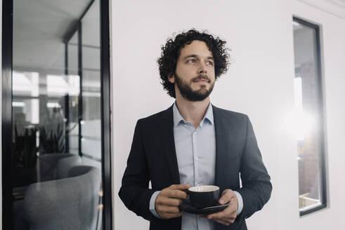 Businessman having a coffee break in office - KNSF06591