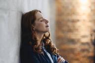 Redheaded businesswoman having a break leaning against a wall in office - KNSF06594