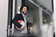 Happy businessman holding beach ball in office - KNSF06597