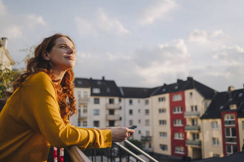 Redheaded woman standing on roof terrace - KNSF06618