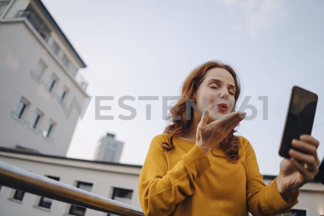 Redheaded woman using cell phone on roof terrace blowing a kiss - KNSF06621 - Kniel Synnatzschke/Westend61