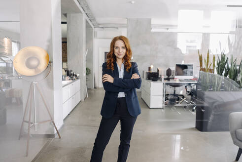 Portrait of confident redheaded businesswoman standing in office - KNSF06633