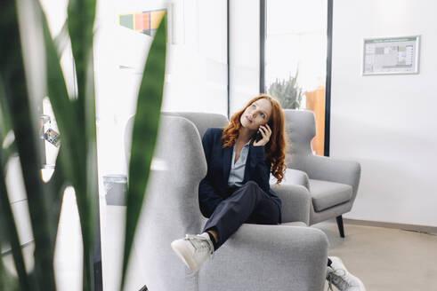 Redheaded businesswoman on the phone in armchair - KNSF06636