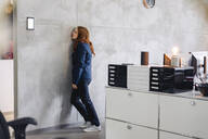 Tired businesswoman leaning against a wall in office - KNSF06642