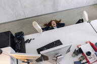 Happy businesswoman lying on the floor in office - KNSF06645