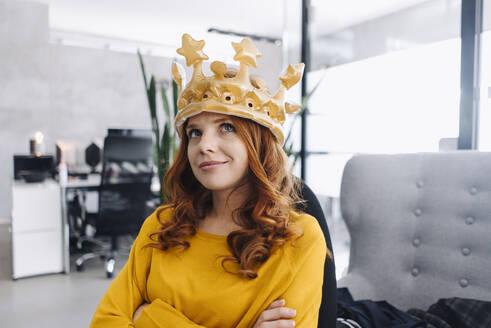 Businesswoman in office wearing a crown - KNSF06648