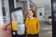 Happy woman with windswept hair on the phone in office - KNSF06654