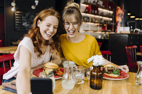 Two happy female friends having burger and taking a selfie in a restaurant - KNSF06660