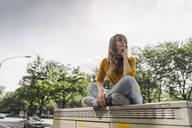 Young woman sitting on a box in the city - KNSF06672