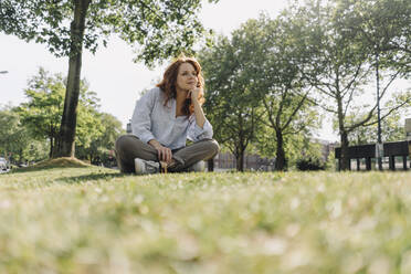 Redheaded woman sitting on grass verge - KNSF06675