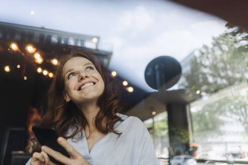 Happy redheaded woman with cell phone in a cafe - KNSF06678