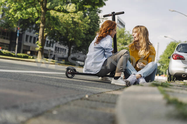 Female friends with e-scooter talking at the roadside in the city - KNSF06687 - Kniel Synnatzschke/Westend61
