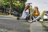 Female friends with e-scooter talking at the roadside in the city - KNSF06687