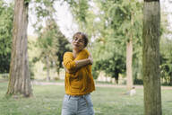 Young woman in a park hugging herself - KNSF06699