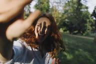 Happy redheaded woman meeting a friend in a park - KNSF06705