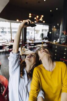 Two happy female friends taking a selfie in a restaurant - KNSF06708