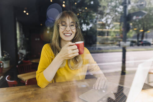 Portrait of smiling woman with laptop and coffee in a cafe - KNSF06714