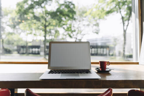 Laptop and cup of coffee on table in a cafe - KNSF06717