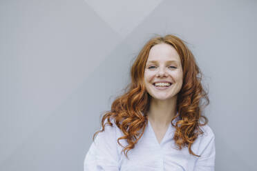 Portrait of happy redheaded woman at a wall - KNSF06720