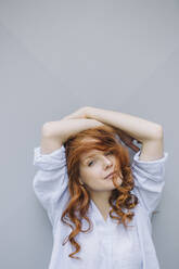Portrait of beautiful redheaded woman at a wall - KNSF06723