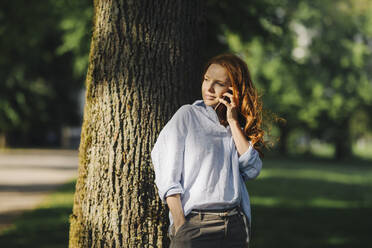 Redheaded woman talking on the phone in park - KNSF06726