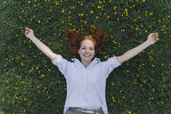 Portrait of happy redheaded woman lying on a flower meadow - KNSF06729
