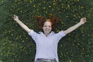 Portrait of happy redheaded woman lying on a flower meadow - KNSF06729
