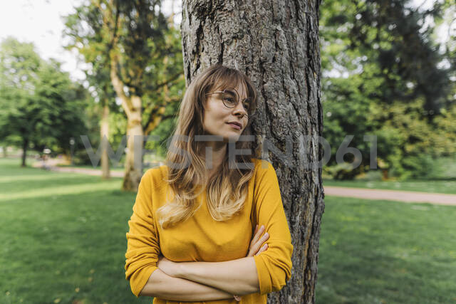 Young woman at a tree in park looking sideways - KNSF06732 - Kniel Synnatzschke/Westend61