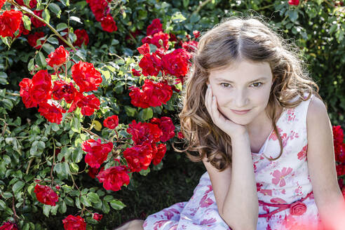 Portrait of girl wearing summerdress with floral design sitting on a meadow beside red rosebush - STBF00406